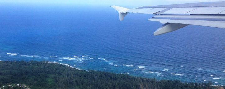 Airplane wing overlooking Caribbean sea and borderland of Aguadilla, Puerto Rico